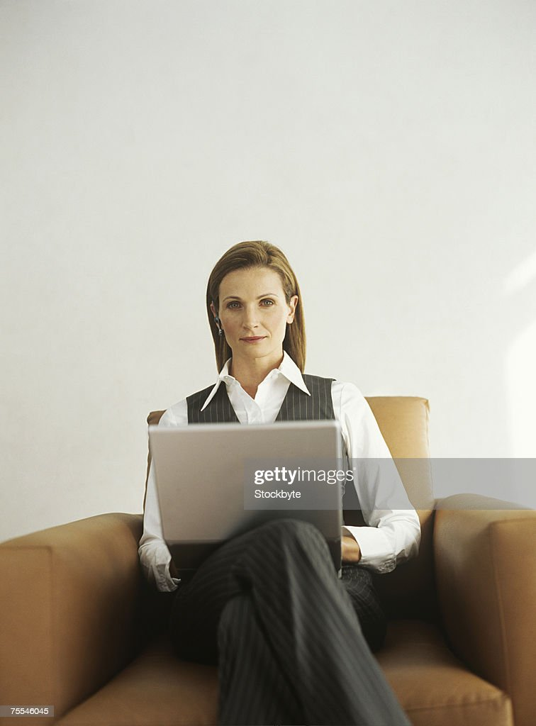Business woman sitting in armchair with laptopportrait for Sitting in armchair