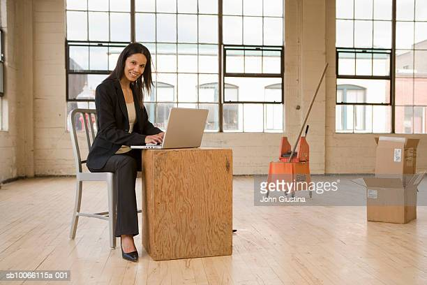 Business woman sitting in empty warehouse using laptop, smiling, portrait