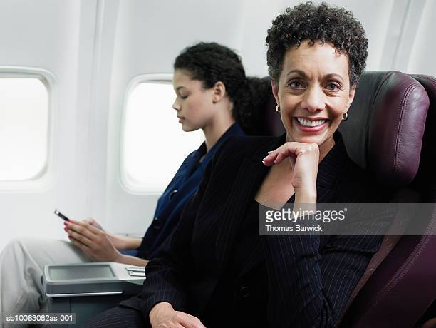 Business woman sitting on airplane smiling, looking at camera, other in background