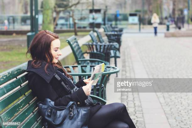 Business woman sitting on bench reading newspaper, city business