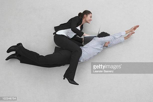 Business woman sitting on flying man's back, using laptop