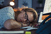 Mature business woman wearing eyeglasses and sleeping on computer keyboard in office. Closeup face of tired businesswoman doing overtime sleeping. Portrait of blonde sleepy woman in dark office. Overw