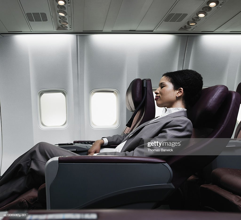 Business woman sleeping on plane, side view