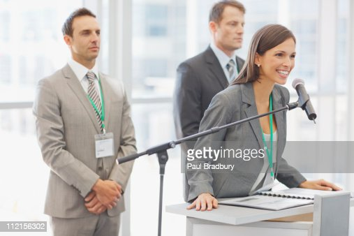 Business woman speaking in to microphone in office : Stock Photo