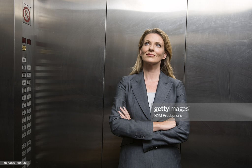 Business woman standing in elevator : Stock Photo