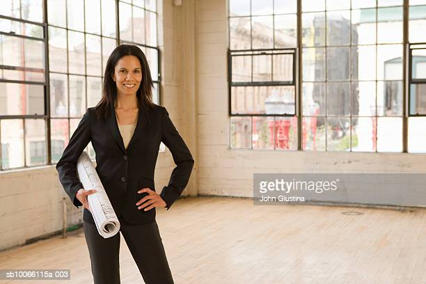 Business woman standing in empty warehouse with blueprints, portrait, smiling