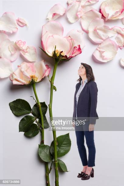Business woman standing next to a big rose