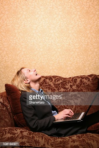 Business woman surfing the net and laughing in Hotel Room : Bildbanksbilder