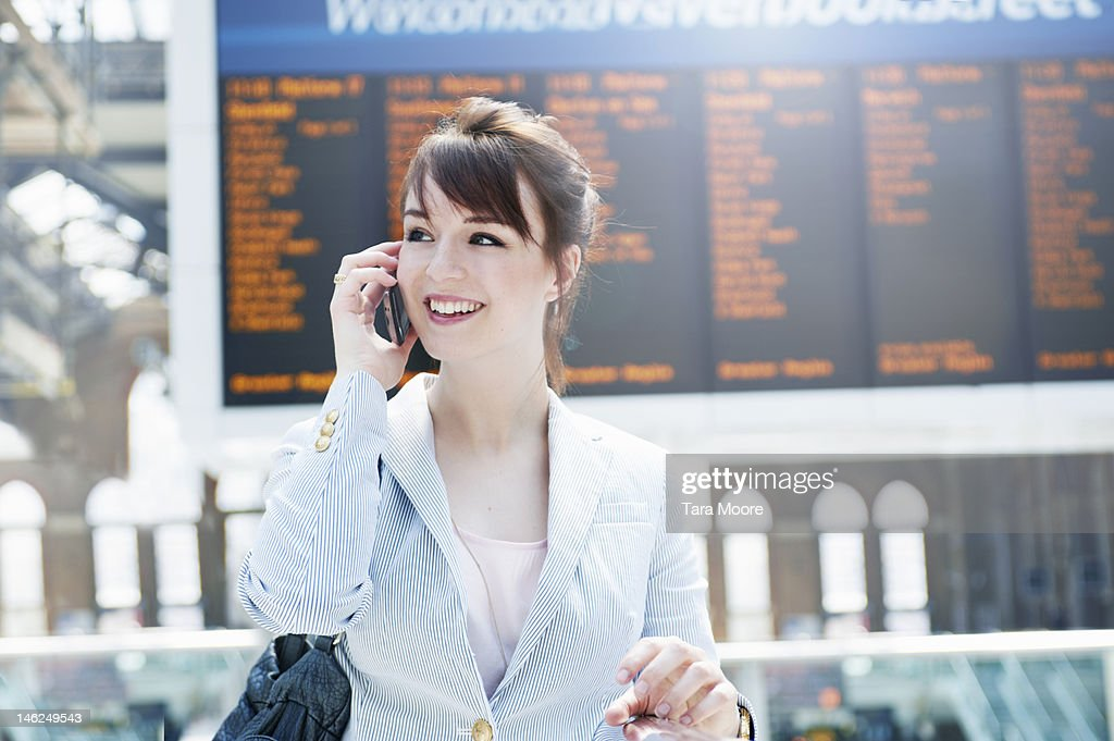 business woman talking on mobile at station : Stock Photo