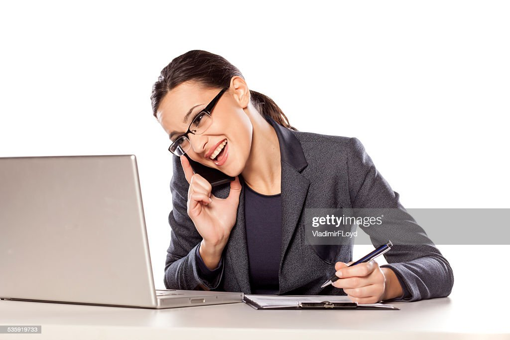 Business woman talking on the phone and writing in notebook : Stock Photo
