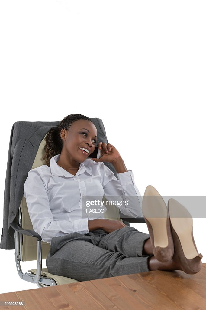 Business woman talking phone at her desk : Stock Photo