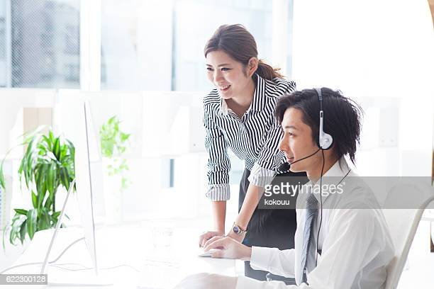 Business woman teaching businessmen at call center