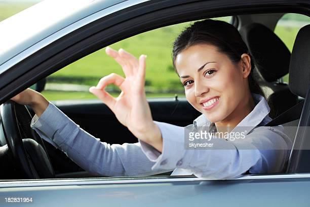 Femme d'affaires à travers la fenêtre de la voiture montrant ok.