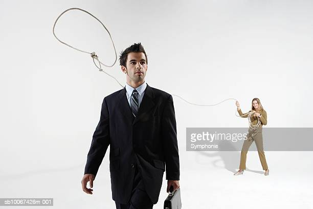 Business woman throwing lasso on male colleague, studio shot