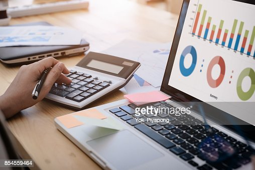 business woman uses a calculator to calculate the company's performance figures, graphs the monthly graphs for the meeting. : Stock Photo