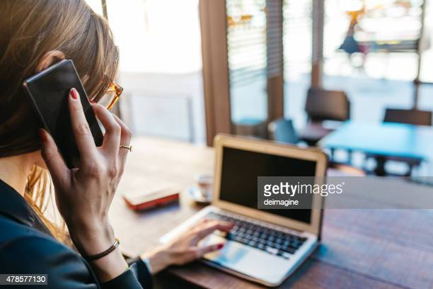 Femme d'affaires utilise un ordinateur portable et un smartphone dans le Café bar