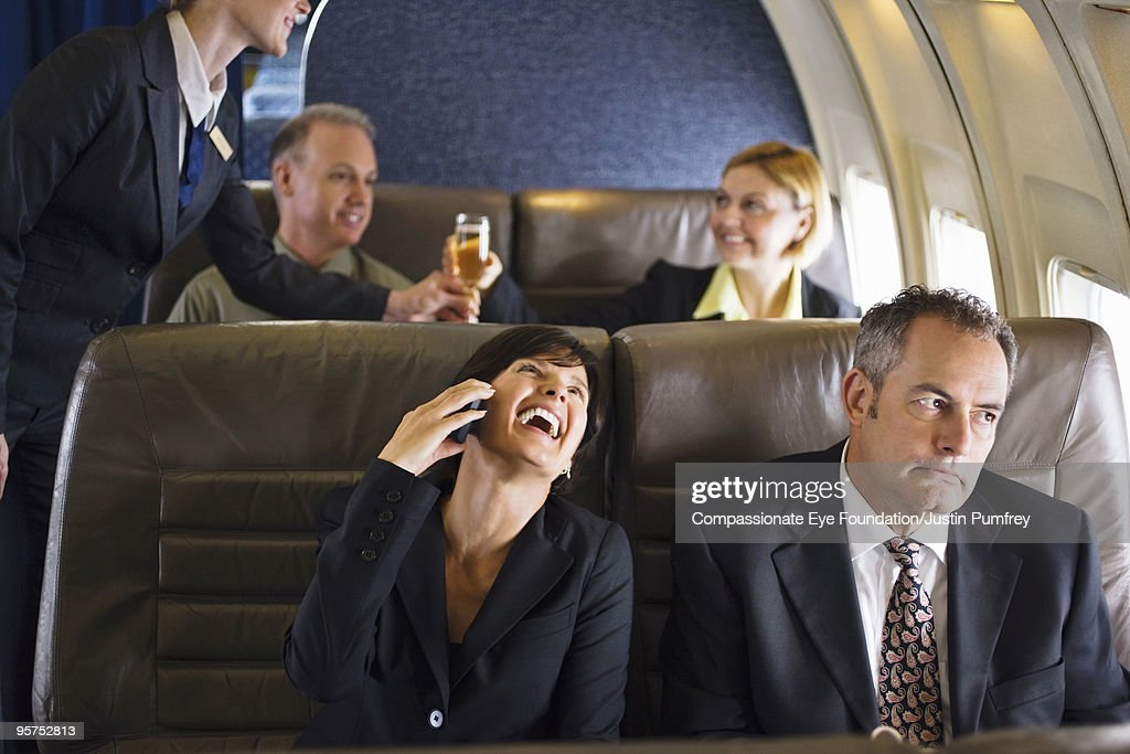 business woman using cell phone on airplane