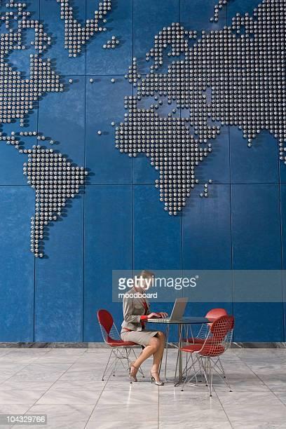 Business-Frau mit laptop im Büro mit Weltkarte