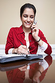 Business woman using mobile phone and writing in diary in office