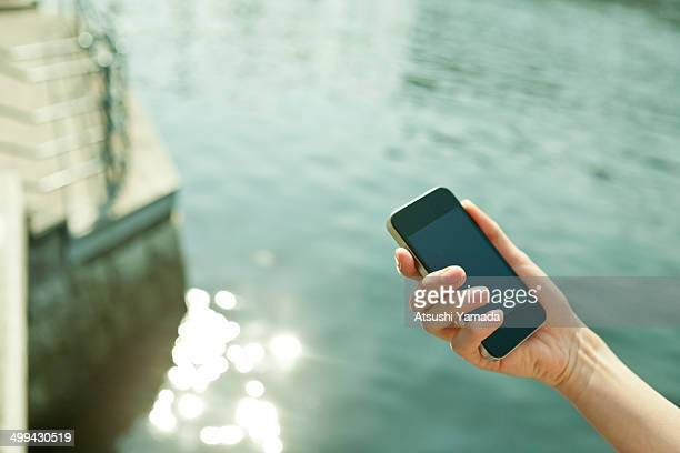 Business woman using smartphone beside river