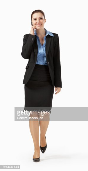 Business woman walking along chatting on phone : Stock Photo