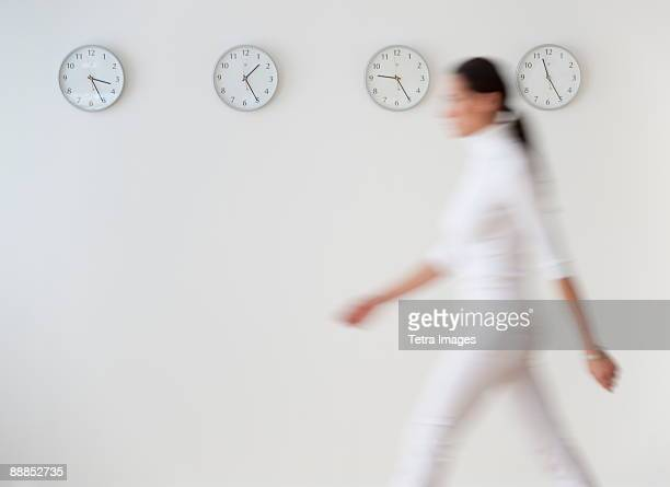 Business woman walking along wall with clocks, blurred motion