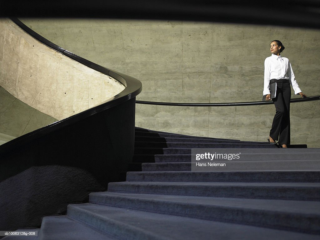Business woman walking down stairs in office, low angle view