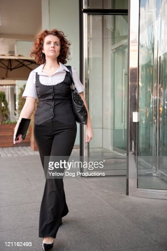 Business woman walking out of office building : ストックフォト