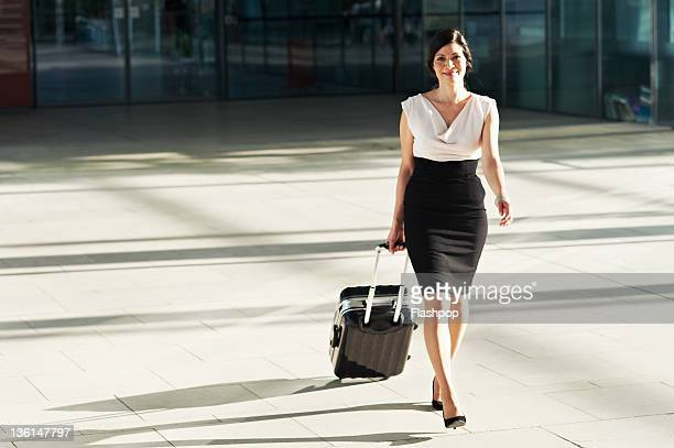 Business woman walking with travel case