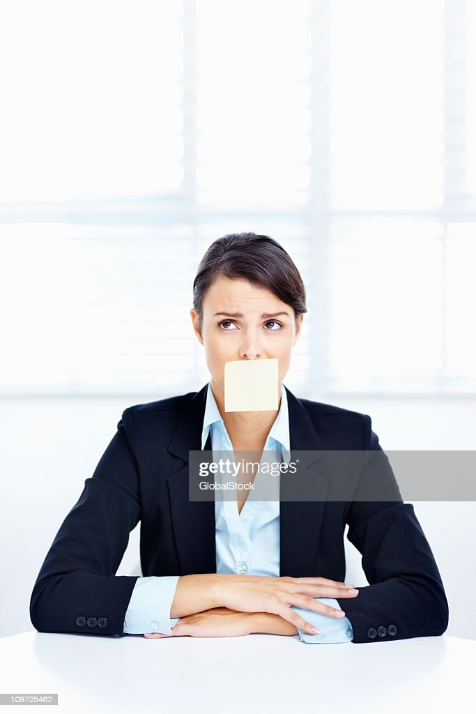 Business woman with a sticky note stuck to her mouth : Stock Photo