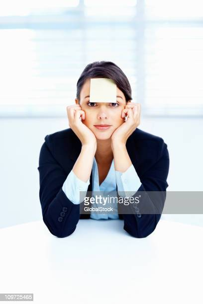 Business woman with an adhesive note on forehead