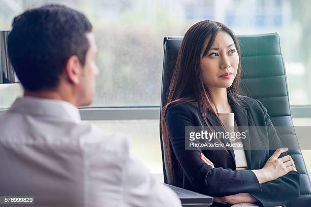 Business woman with arms folded looking away with air of disappointment
