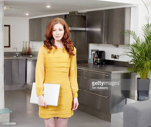 Business woman with laptop in modern kitchen.