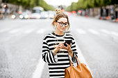 Young stylish woman in striped sweater using a smart phone standing outdoors on the street in Paris