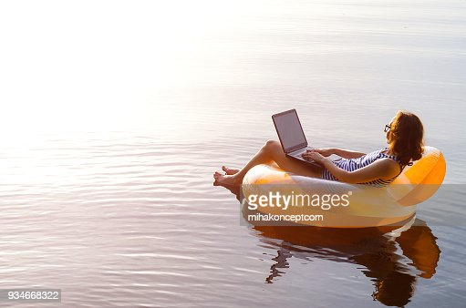 Business woman working on a laptop in an inflatable ring in the water, a copy of the free space. Workaholic, work on vacation. : Stock Photo
