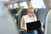 Businesswoman talking on cellphone and working on laptop while traveling by train. Business travel concept.