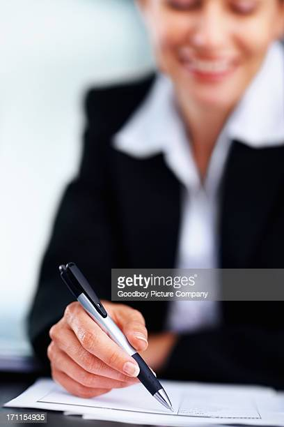 Business woman writing notes, focus on pen