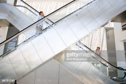 Business women and man on escalator