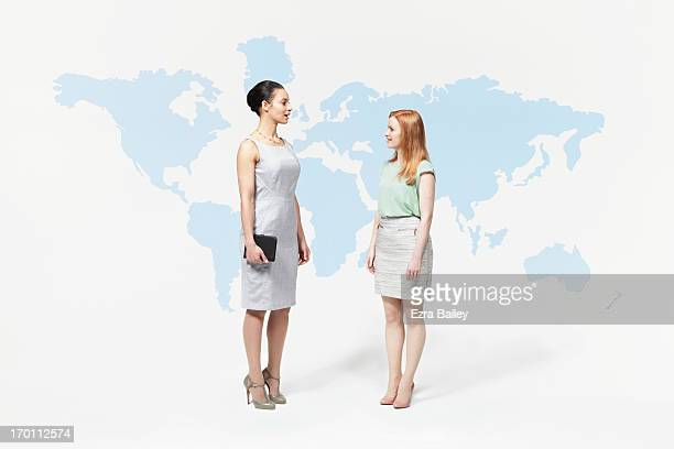 Business women chatting in front of world map.