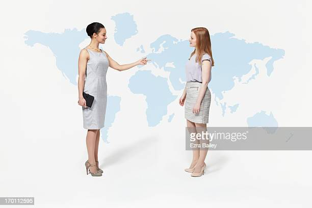 Business women interacting with world map.