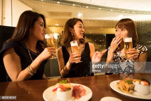 ビジネスの女性は、ビールを飲みながら話します。