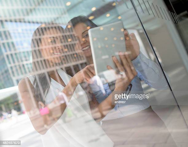 Business women working at the office using a tablet