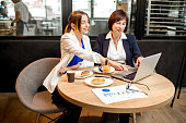 Senior business woman with young partner dressed in suits working with laptop during a coffee time in the modern cafe