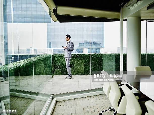 Businessma with smartphone on office terrace
