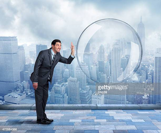 Businessman about to pop a large bubble