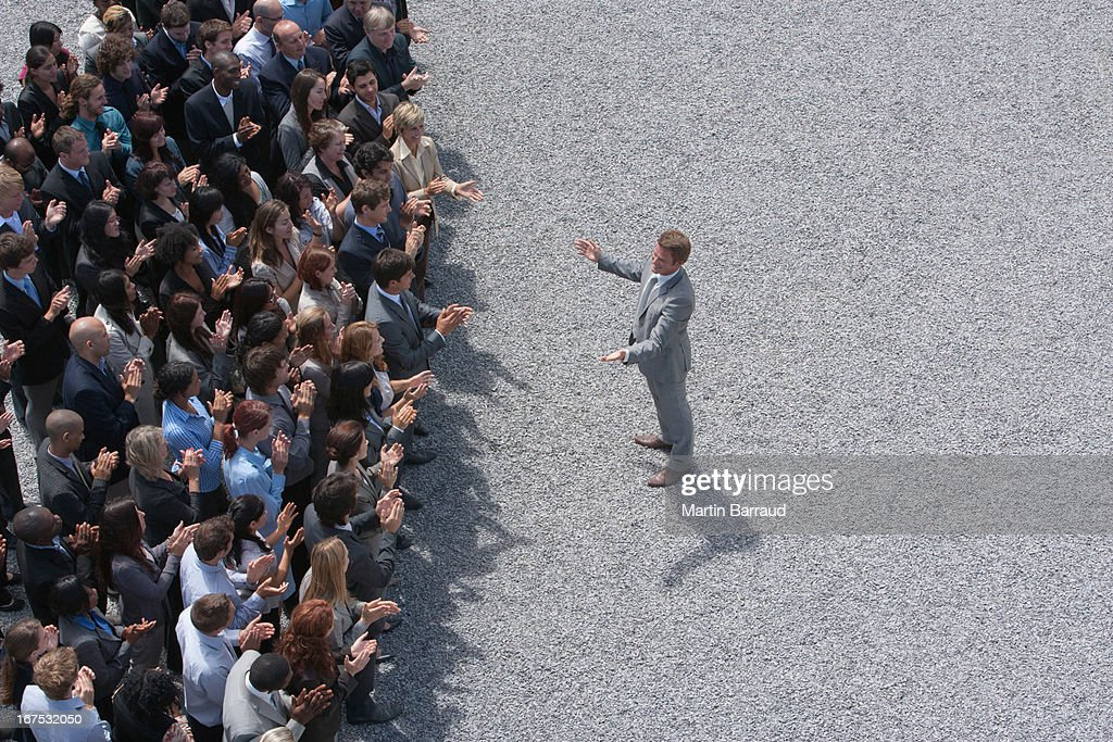 Businessman addressing clapping crowd : Stock Photo