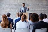 Businessman Addressing Delegates At Conference