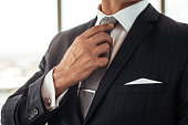 Cropped shot of businessman hand adjusting his necktie. Close up of man in business suit correcting tie.