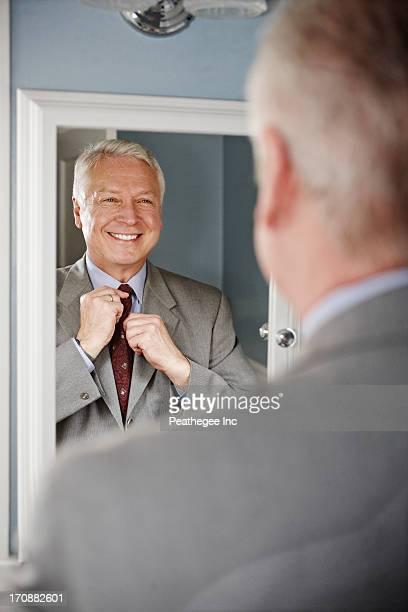 Businessman adjusting his tie in mirror