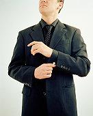Businessman adjusting sleeve